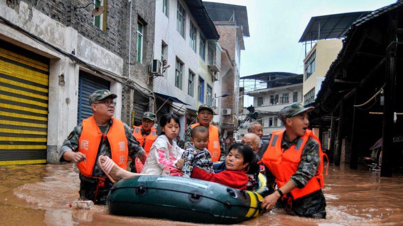 Foto tomada el 28 de junio de 2020 muestra a los rescatistas evacuando a los residentes en un área inundada después de fuertes lluvias al suroeste de Chongqing en China. (STR/AFP/Getty Images)