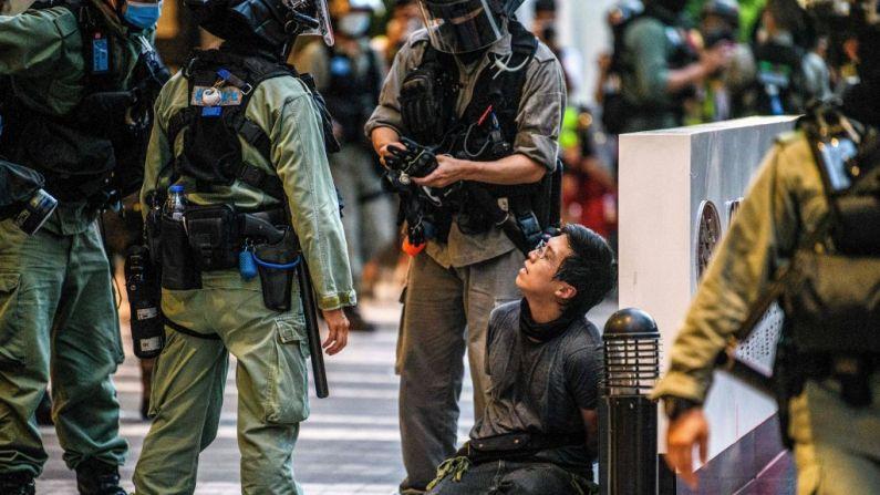 Un manifestante (centro) es detenido por la policía durante una manifestación contra una nueva ley de seguridad nacional en Hong Kong el 1 de julio de 2020, en el 23º aniversario del traspaso de la ciudad de Gran Bretaña a China. (Foto de ANTHONY WALLACE/AFP a través de Getty Images)