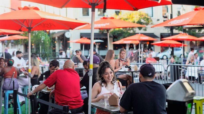 Los clientes cenan en un restaurante al aire libre en la 5ª Avenida en el barrio de Gaslamp en el centro de San Diego, California, el 17 de julio de 2020. (Foto de SANDY HUFFAKER/AFP vía Getty Images)
