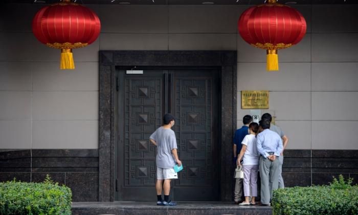 Varias personas intentan hablar con alguien en el consulado chino de Houston el 22 de julio de 2020. (Mark Felix/AFP vía Getty Images)