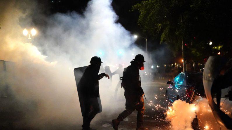Alborotadores corren hacia una lata de gas lacrimógeno mientras se enfrentan a agentes federales cerca del juzgado Mark O. Hatfield el 24 de julio de 2020 en Portland, Oregon. (Nathan Howard/Getty Images)