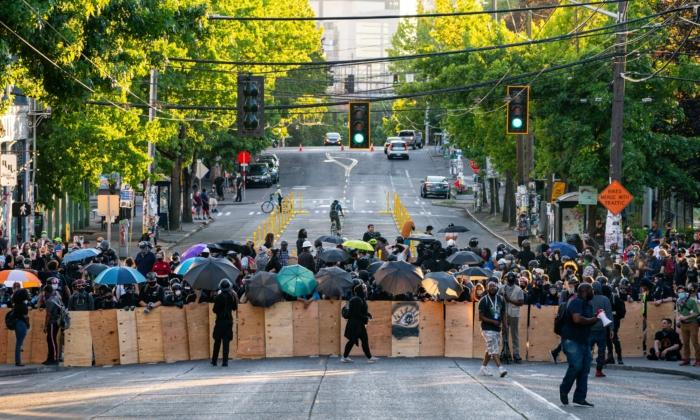 Los manifestantes usan escudos mientras bloquean una intersección cerca de la Comisaría Este de la Policía de Seattle durante las protestas en Seattle el 26 de julio de 2020 en Seattle, Washington. (David Ryder/Getty Images)