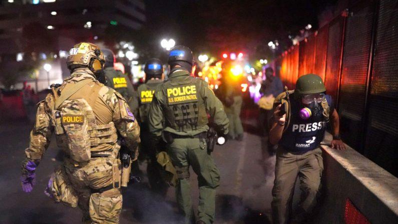 Un periodista pasa frente a los oficiales federales, el 30 de julio de 2020, en Portland, Oregon. (Nathan Howard/Getty Images)