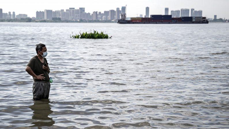 Un residente parada dentro del agua cerca del parque de Jiangtan, el cual se inundó debido a las fuertes lluvias a lo largo del río Yangtsé, el 8 de julio de 2020 en Wuhan, China. (Foto de Getty Images)