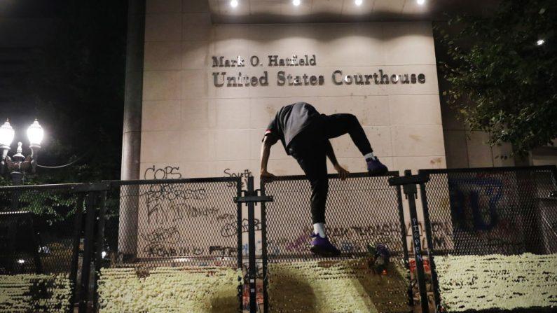 Un alborotador sube la valla frente al juzgado federal Mark O. Hatfield en el centro de Portland mientras la ciudad experimenta otra noche de disturbios el 26 de julio de 2020 en Portland, Oregon. (Spencer Platt/Getty Images)