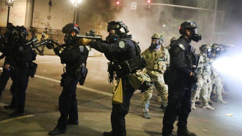 Los federales se enfrenta a los alborotadores frente al juzgado federal Mark O. Hatfield en el centro de Portland mientras la ciudad experimenta otra noche de disturbios el 27 de julio de 2020 en Portland, Oregon. (Spencer Platt/Getty Images)