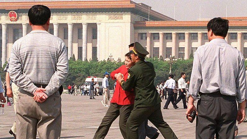 Policías vestidos de civil observan cómo una mujer practicante de Falun Gong es llevada a la fuerza por la policía hacia una camioneta policial, el 11 de mayo de 2000 en la Plaza Tiananmen de Beijing. (STEPHEN SHAVER/AFP a través de Getty Images)