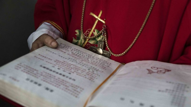 "Un diácono católico chino sostiene una biblia en la Misa del Domingo de Ramos durante la Semana Santa de Pascua en una iglesia ""clandestina"" o ""no oficial"" cerca de Shijiazhuang, provincia de Hebei, China, el 9 de abril de 2017. (Kevin Frayer/Getty Images)"