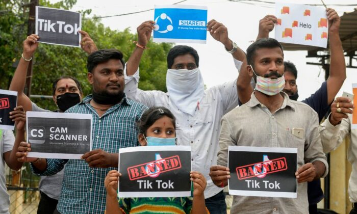 """Miembros de la City Youth Organisation sostienen carteles con los logotipos de aplicaciones chinas en apoyo al gobierno de la India por la prohibición de la tan popular aplicación para compartir videos """"Tik Tok"""", en Hyderabad el 30 de junio de 2020. (Noah Seelam/AFP vía Getty Images)"""