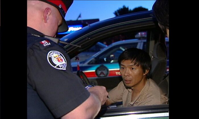 La policía de Toronto interroga a Lu Ping sobre su entrega del folleto informativo contra Falun Gong de Crescent Chau el 30 de junio de 2007 en la tienda Asian Farm del noreste de Toronto. (NTDTV)