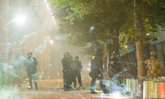 Algunos fuegos artificiales estallan cerca de los agentes federales que vigilan el juzgado federal de Mark O. Hatfield en el centro de Portland mientras ellos se enfrentan a los alborotadores en Portland, Oregon, EStados Unidos, el 24 de julio de 2020. (Kathryn Elsesser/AFP vía Getty Images)