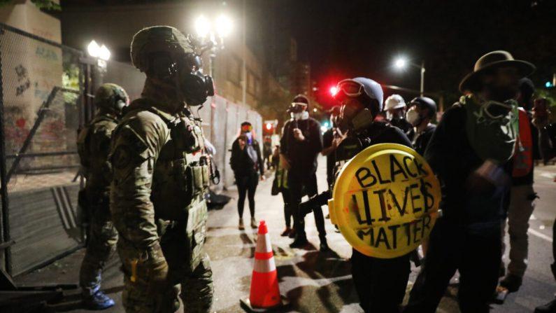 Agentes federales se enfrentan a los alborotadores frente a la corte federal Mark O. Hatfield en Portland, Ore., el 26 de julio de 2020. (Spencer Platt/Getty Images)