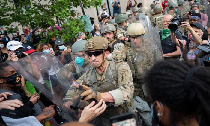 Manifestantes se pelean con los miembros del ejército de EE.UU. mientras protestan por la muerte de George Floyd cerca de la Casa Blanca en Washington el 3 de junio de 2020. (Jim Watson/AFP vía Getty Images)