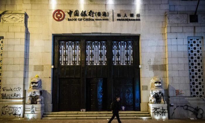 Un hombre pasa junto a un graffiti hecho por manifestantes en el viejo edificio del Banco de China después de una manifestación prodemocracia en Hong Kong el 8 de diciembre de 2019. (Anthony Wallace/AFP vía Getty Images)