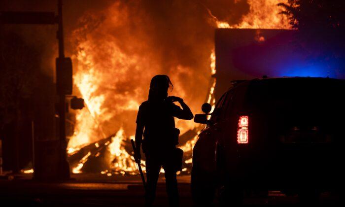 Un policía vigila una casa de empeños saqueada en llamas en Minneapolis, Minnessota, el 28 de mayo de 2020. (Stephen Maturen/Getty Images)