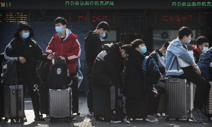 BEIJING, CHINA - Estudiantes chinos usan mascarillas mientras esperan a tomar un tren después de las vacaciones de Año Nuevo chino en Beijing, China, el 31 de enero de 2020. (Kevin Frayer/Getty Images)