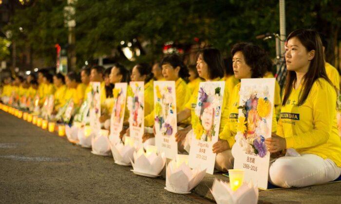 Los practicantes de Falun Gong realizan una vigilia a la luz de las velas frente al consulado chino en Toronto el 13 de julio de 2019, con fotos de sus compañeros practicantes que fueron asesinados bajo la persecución en China. (Handout)