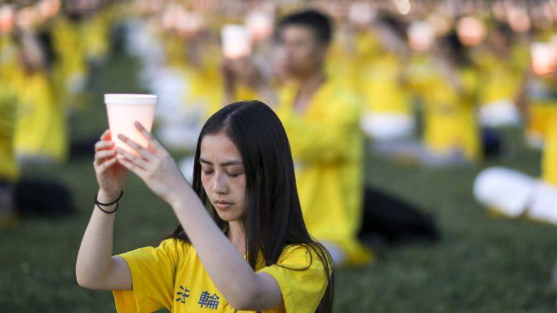 Practicantes de Falun Gong participan en una vigilia de velas en conmemoración del 20º aniversario de la persecución de Falun Gong en China, en el jardín occidental del Capitolio el 18 de julio de 2019. (Samira Bouaou/The Epoch Times)
