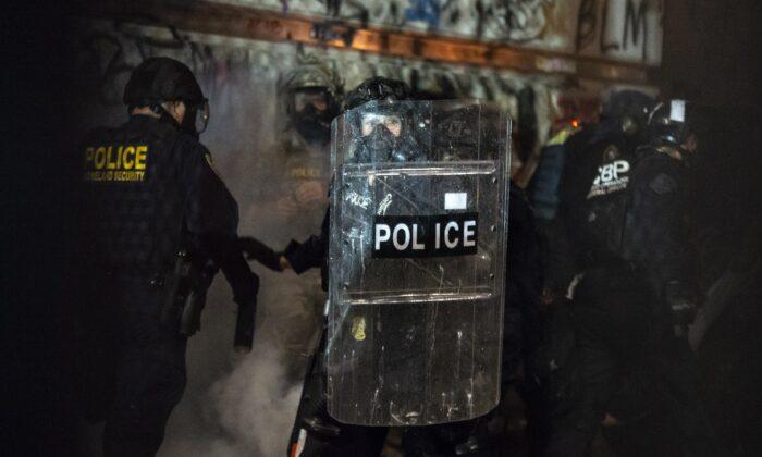 Un policía federal se cubre detrás de un escudo mientras se enfrenta a los alborotadores en la Corte de Mark O. Hatfield en Portland, Ore., el 23 de julio de 2020. (Nathan Howard/Getty Images)