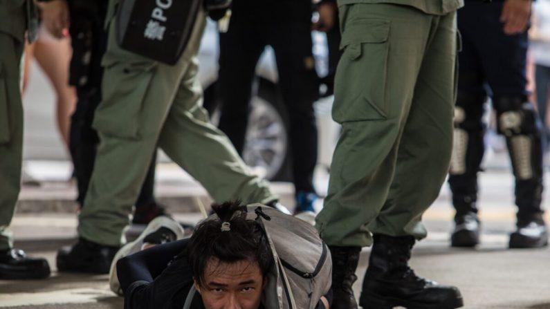 La policía antidisturbios detiene a un hombre, mientras expulsan a los manifestantes que participan en una manifestación contra una nueva ley de seguridad nacional en Hong Kong, el 1 de julio de 2020, en el 23° aniversario de la entrega de la ciudad de Gran Bretaña a China. (Dale de la Rey/AFP a través de Getty Images)