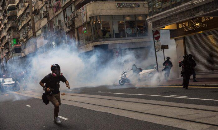 La policía antidisturbios despliega gas lacrimógeno mientras despeja a los manifestantes de una carretera durante una manifestación contra una nueva ley de seguridad nacional en Hong Kong el 1 de julio de 2020, en el 23º aniversario del traspaso de la ciudad de Gran Bretaña a China. (Dale de la Rey/AFP vía Getty Images)