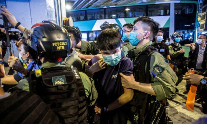 Un agente de la policía antidisturbios (dcha.) detiene a un hombre (centro) durante una protesta en un centro comercial de Yuen Long en Hong Kong el 19 de julio de 2020. (Isaac Lawrence/AFP vía Getty Images)