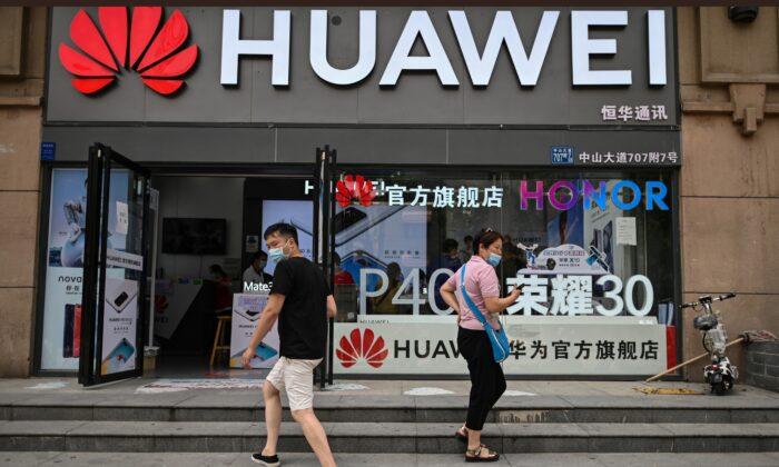 Personas con mascarillas caminan fuera de una tienda Huawei en la ciudad de Wuhan, provincia de Hubei, China, el 26 de mayo de 2020. (HECTOR RETAMAL/AFP vía Getty Images)