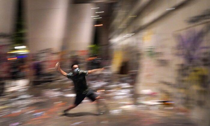 Un alborotador arroja una botella de agua a la sede de la corte Mark O. Hatfield después de que los agentes federales se refugiaran dentro en Portland, Ore., el 21 de julio de 2020. (Nathan Howard/Getty Images)