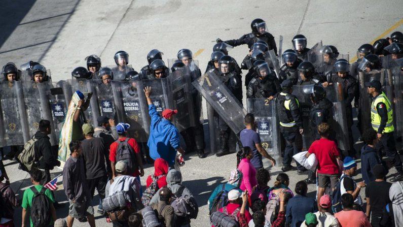 Migrantes centroamericanos son bloqueados por fuerzas policiales mexicanas cuando llegan al paso fronterizo de El Chaparral, en Tijuana, estado de Baja California, México, el 25 de noviembre de 2018. (Pedro Pardo/AFP/Getty Images)