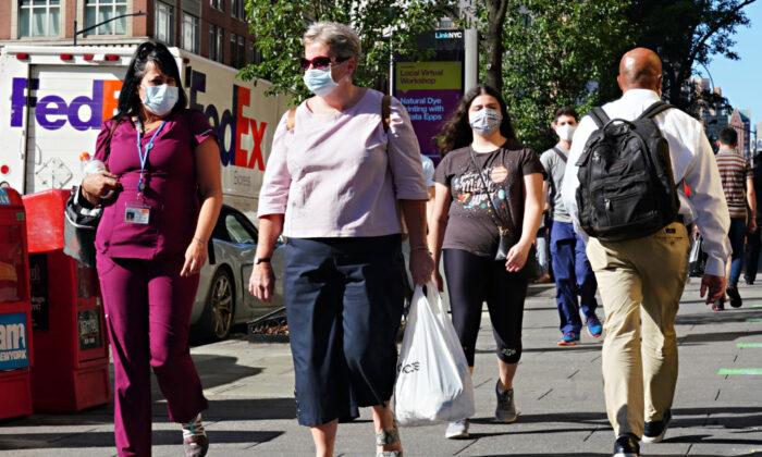 La gente camina con mascarillas protectoras mientras la ciudad de Nueva York pasa a la fase 3 de reapertura tras las restricciones impuestas para frenar la pandemia del virus del PCCh el 14 de julio de 2020. (Cindy Ord/Getty Images)