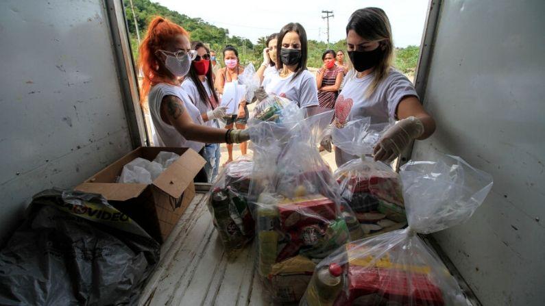 """Voluntarios de """"Por Gentileza"""" ayudan a organizar donaciones de alimentos para los residentes de la comunidad de Itaoca en medio de la pandemia del coronavirus (COVID-19) el 6 de junio de 2020 en Sao Goncalo, Brasil. (Luis Alvarenga/Getty Images)"""