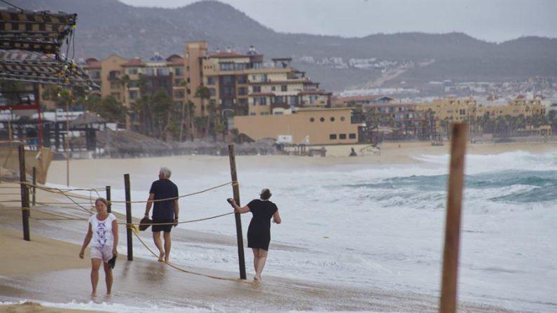 Un grupo de personas camina por una playa frente a fuertes olas en Cabo San Lucas el estado mexicano de Baja California Sur. EFE/Archivo