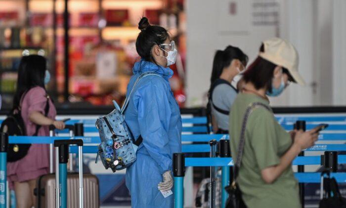 Un viajero con equipo de protección y una mascarilla espera en fila en el mostrador de una aerolínea en el aeropuerto de Tianhe en Wuhan, en la provincia de Hubei, al centro de China, el 23 de mayo de 2020. (Hector Retamal/AFP vía Getty Images)