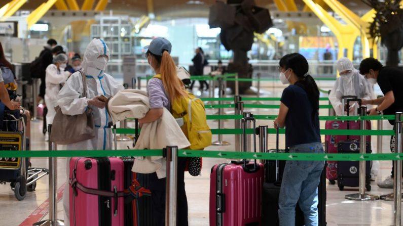 Pasajeros esperan para facturar en el aeropuerto de Barajas en Madrid el 20 de junio de 2020, un día antes de que termine el estado de emergencia del país tras un cierre nacional para detener la propagación del virus del PCCh. (Foto de PIERRE-PHILIPPE MARCOU/AFP vía Getty Images)