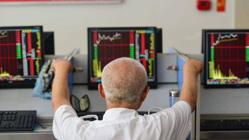 Un inversor mira las pantallas que muestran los movimientos del mercado de valores en una compañía de valores en Fuyang, en la provincia oriental de Anhui de China, el 6 de julio de 2020. (STR/AFP vía Getty Images)