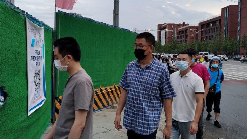 La gente usa mascarillas mientras espera en fila para someterse a las pruebas de hisopado del coronavirus COVID-19 en una estación de pruebas temporal en Beijing el 6 de julio de 2020. (Lintao Zhang/Getty Images)