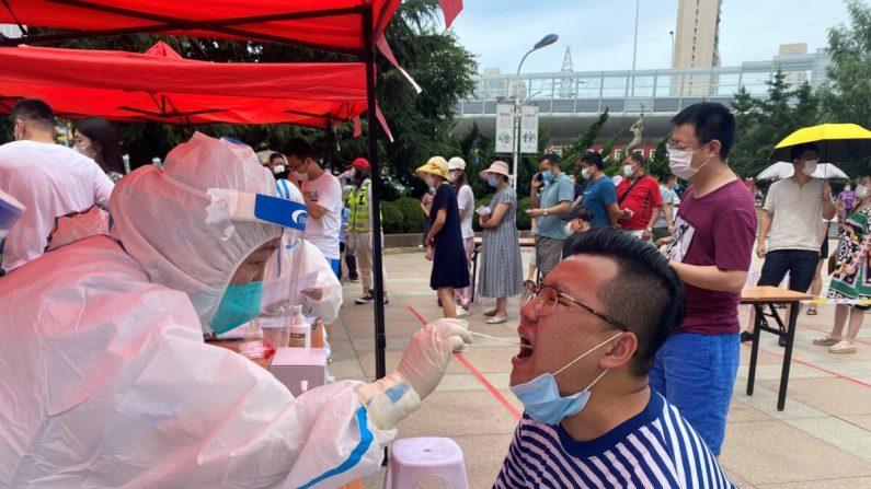 Un trabajador de la salud está llevando a cabo una prueba de COVID-19 en Dalian, en la provincia de Liaoning, en el noreste de China, el 26 de julio de 2020. (STR/AFP a través de Getty Images)