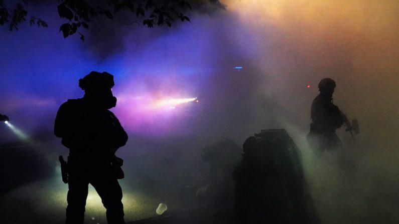 Agentes federales hacen guardia mientras un manifestante es arrestado en una nube de gas lacrimógeno durante una protesta contra la injusticia racial y la brutalidad policial frente a la Corte de Estados Unidos Mark O. Hatfield en Portland, Oregon, en la madrugada del 30 de julio de 2020. (Nathan Howard/Getty Images)