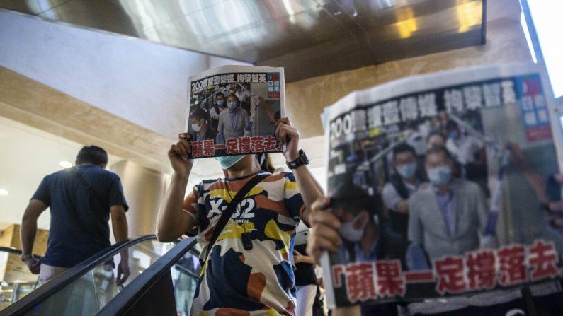 La gente sostiene copias del Apple Daily mientras protestan por la libertad de prensa dentro de un centro comercial en Hong Kong, el 11 de agosto de 2020. (ISAAC LAWRENCE/AFP vía Getty Images)