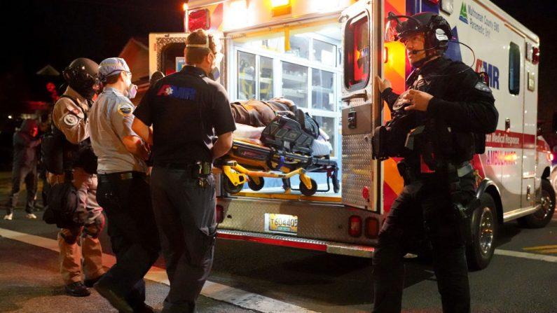 Un oficial de policía de Portland observa a la multitud mientras los médicos ayudan a un manifestante, que se cayó y se golpeó la cabeza frente a la Oficina del Sheriff del condado de Multnomah, el 11 de agosto de 2020, en Portland, Oregon. (Nathan Howard/Getty Images)