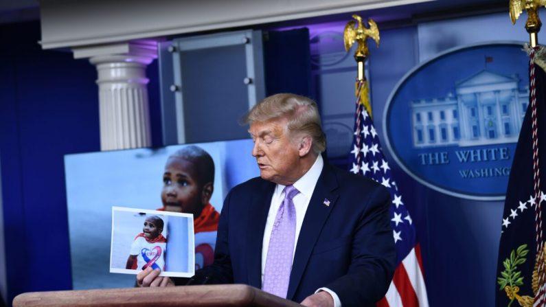 El presidente Donald Trump sostiene una foto de LeGend Taliferro, víctima de un crimen, durante una conferencia de prensa en la Sala Brady Briefing de la Casa Blanca en Washington el 13 de agosto de 2020. (Brendan Smialowski / AFP/Getty Images)