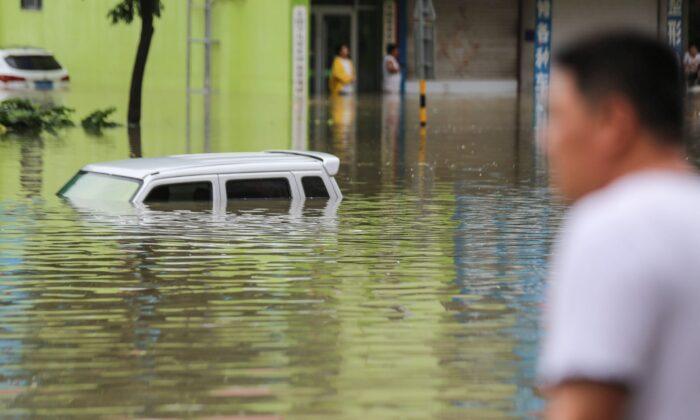Un hombre mira los vehículos atascados en una calle inundada después de que las fuertes lluvias azotaran el área en Linyi, en la provincia oriental de Shandong, el 14 de agosto de 2020 (STR / AFP a través de Getty Images).