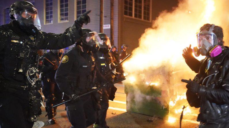 Oficiales de policía de Portland empujan a los manifestantes más allá del fuego de un contenedor de basura durante una dispersión frente al centro de detención del Servicio de Inmigración y Aduanas (ICE) en la madrugada del 21 de agosto de 2020 en Portland, Oregon. Por segunda noche consecutiva, la policía de la ciudad y los oficiales federales se enfrentaron a los manifestantes en el South Waterfront. (Nathan Howard/Getty Images)
