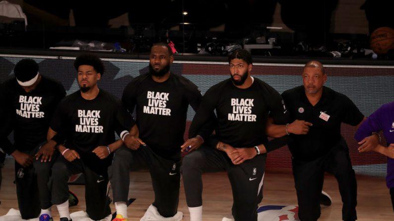 LeBron James (centro) y Anthony Davis (2do derecha) de Los Angeles Lakers con una camiseta de Black Lives Matter se arrodillan con sus compañeros de equipo durante el himno nacional antes del partido contra los Clippers de LA el 30 de julio de 2020 en Lake Buena Vista, Florida. (Mike Ehrmann/Getty Images)