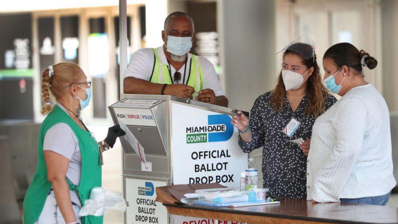 Trabajadores electorales ayudan a un votante a colocar su boleta de voto por correo en una urna oficial del condado de Miami-Dade el 11 de agosto de 2020 en Miami, Florida. (Foto de Joe Raedle/Getty Images)