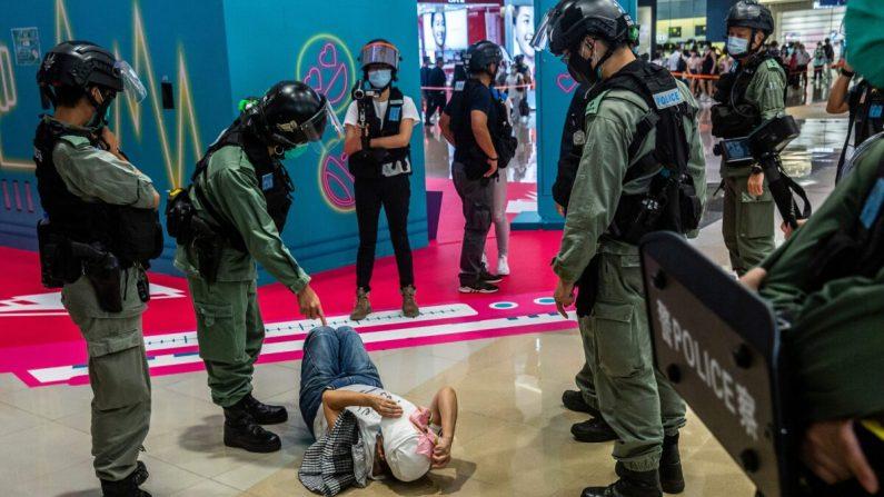 Un agente de la policía antidisturbios (2I) señala a una mujer acostada después de haber sido registrada durante una manifestación en un centro comercial de Hong Kong el 6 de julio de 2020, en respuesta a la nueva ley de seguridad nacional de Beijing. (Isaac Lawrence/AFP vía Getty Images)