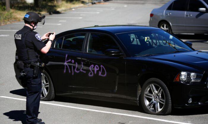 """Un policía de Seattle fotografía un graffiti que dice """"matar a SPD"""" en el Centro de Detención Juvenil del condado de King en Seattle, Washington, el 25 de julio de 2020. (Jason Redmond/AFP vía Getty Images)"""
