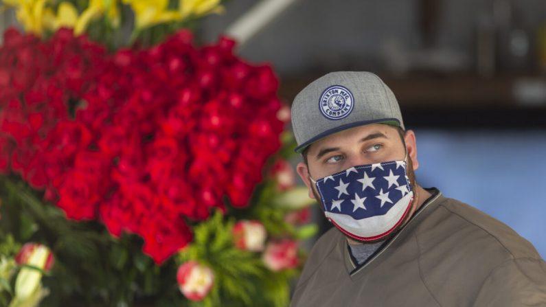 Un hombre usa una cubierta de cara patriótica en el distrito de las flores en el centro de Los Ángeles, California, el 8 de mayo de 2020. (David McNew/Getty Images)