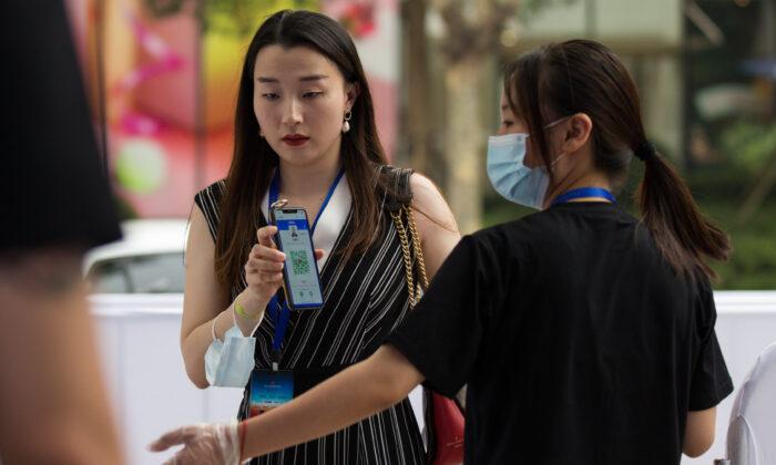 Un trabajador del personal usa mascarillas protectoras mientras verifica el código QR saludable de una audiencia en la entrada antes de un evento de proyección al aire libre en Shanghai, China, el 25 de julio de 2020 (Yifan Ding/Getty Images)