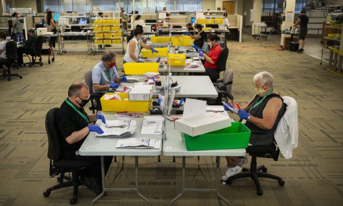 Los trabajadores electorales procesan las boletas electorales por correo para las elecciones primarias de Washington en la sede de King County Elections en Renton, Washington, el 4 de agosto de 2020. (David Ryder/Getty Images)